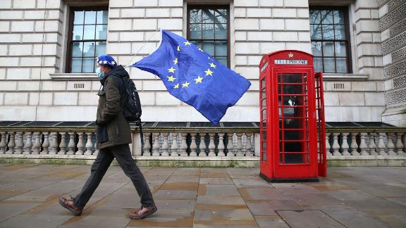 "A man wearing an EU flag-themed beret and carrying an EU flag is seen on Whitehall in central London on December 11, 2020. - Prime Minister Boris Johnson on December 10 vowed to go the ""extra mile"" for a Brexit trade deal but instructed his government to prepare for Britain to crash out of the European Union"