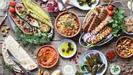 Vibrant foods like roasted red pepper dip and pomegranate make for an eye-catching Mediterranean spread.