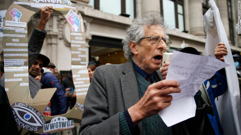 Piers Corbyn speaks to demonstrators as a man holds up a QAnon sign behind him during a StandUpX protest in London this October.