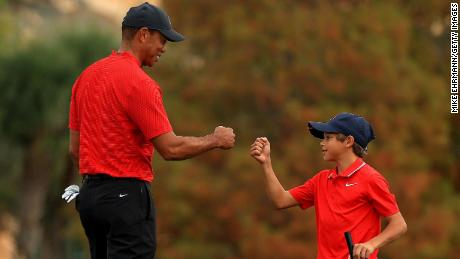 Tiger fist bumps Charlie on the 18th hole of the final round of the PNC Championship.