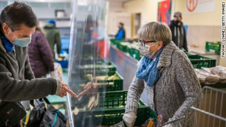 People receive fruit and vegetables from volunteers at a Tafel food bank in Schweinfurt, Germany in November.