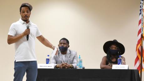 T.I. speaks at a Las Vegas summit on race and policing in June, as activist Kyle West and comedian Lady A.K. McMorris look on.