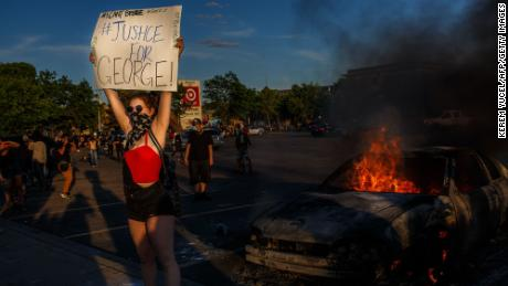 "A protester hold sign board ""Justice for George"" into a fire outside a Target store near the Third Police Precinct on May 28, 2020 in Minneapolis, Minnesota, during a demonstration over the death of George Floyd."