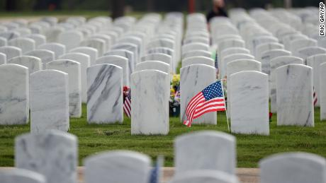 A flag waves in a sea of headstones at the Fort Sam Houston National Cemetery in San Antonio on May 21, 2020.