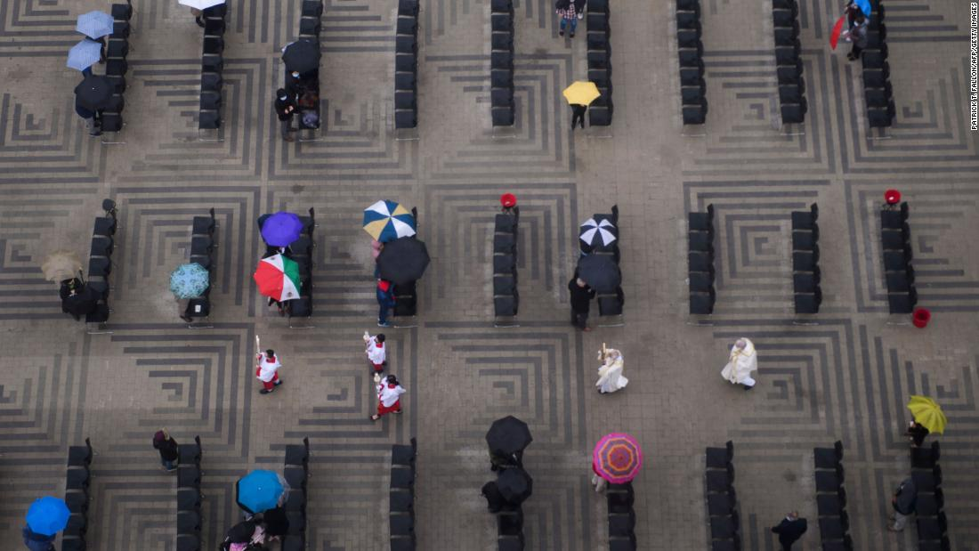 This aerial photo shows a Christmas Eve Mass at the Christ Cathedral in Garden Grove, California. The congregation was social distancing and carrying umbrellas during the outdoor event.