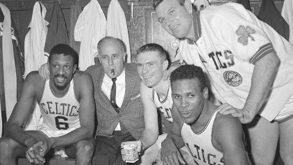 In this April 9, 1964, file photo, Boston Celtics, from left, Bill Russell, coach Red Auerbach, Tommy Heinsohn, Jim Locustoff, and K.C. Jones celebrate in the locker room after clinching their eighth straight Eastern Division playoff title at the Boston Garden in Boston.