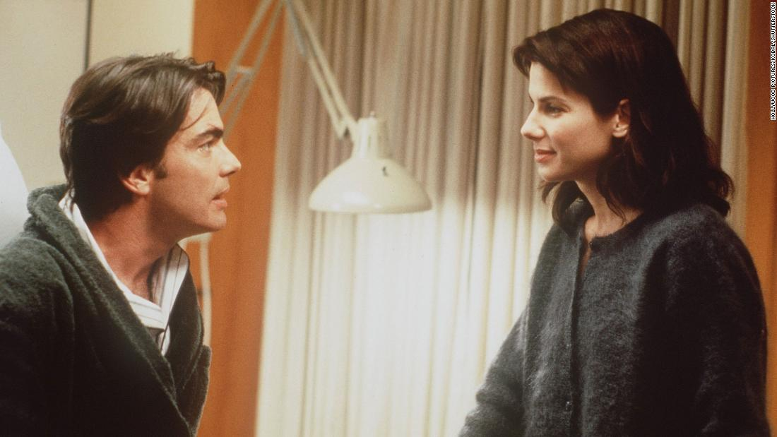 "Sandra Bullock (right) stars as lonely transit worker Lucy Eleanor Moderatz, who is mistaken as the fiancée of coma patient Peter Callaghan (played by Peter Gallagher, left), in the 1995 film ""While You Were Sleeping."""
