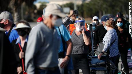 Seniors and first responders wait in line to receive a Covid-19 vaccine at Lakes Regional Library on December 30, 2020, in Fort Myers, Florida.