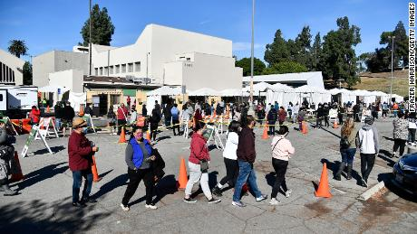 People wait in line at a coronavirus testing and vaccination site on December 30, 2020 in Los Angeles, California.
