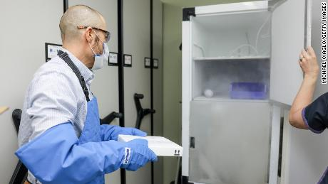 A pharmacist moves 975 doses of the Pfizer-BioNTech Covid-19 vaccine to a freezer on December 15, 2020 in Aurora, Colorado.