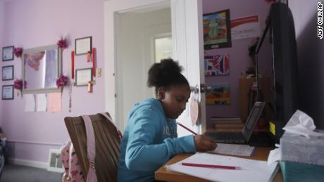 In this April 9, 2020, file photo, Sunnyside Elementary School fourth-grader Miriam Amacker does school work in her room at her family's home in San Francisco.