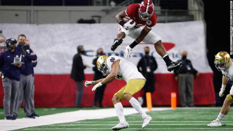 Alabama's Najee Harris hurdles over a Notre Dame defender after Megan Rapinoe tells him to