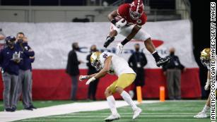 Alabama's Najee Harris hurdles over a Notre Dame defender after Megan Rapinoe tells him to