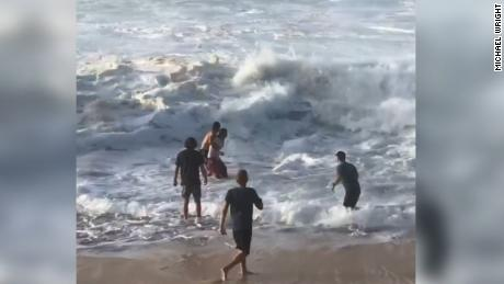 Wright holds onto the unidentified woman in the water to prepare for an oncoming wave as they make their way to shore.