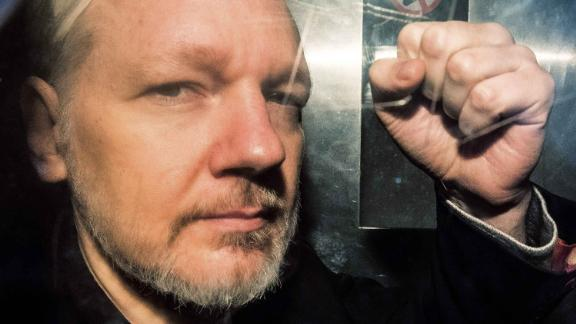 Assange gestures from the window of a prison van as he is driven into Southwark Crown Court in London on May 1, 2019, before being sentenced to 50 weeks in prison for breaching his bail conditions in 2012.