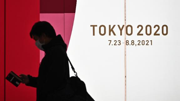 A man walks along a corridor past an official Tokyo 2020 Summer Olympics advertisement board in the Shinjuku district of Tokyo on November 30, 2020. (Photo by Philip FONG / AFP) (Photo by PHILIP FONG/AFP via Getty Images)