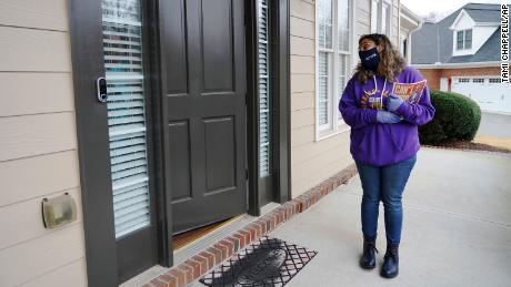 Stephanie Lopez-Burgus talks to a voter while canvassing in Lawrenceville, Georgia.
