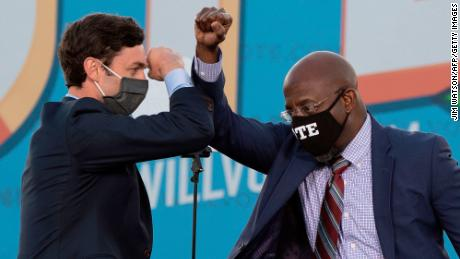 Jon Ossoff, left and Raphael Warnock bump elbows at a rally with US President-elect Joe Biden in Atlanta on January 4.