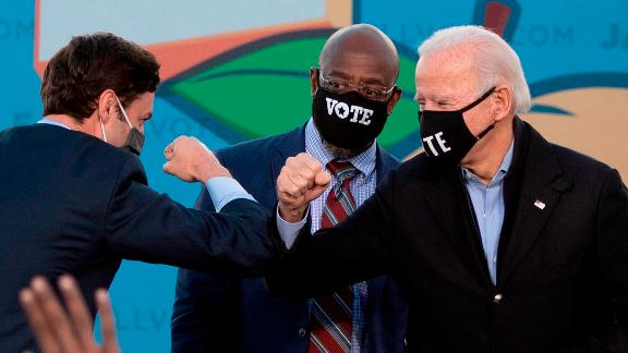 Democratic candidates for Senate Jon Ossoff (L), Raphael Warnock (C) and US President-elect Joe Biden (R) bump elbows on stage during a rally outside Center Parc Stadium in Atlanta, Georgia, on January 4, 2021. - President Donald Trump, still seeking ways to reverse his election defeat, and President-elect Joe Biden converge on Georgia on Monday for dueling rallies on the eve of runoff votes that will decide control of the US Senate. Trump, a day after the release of a bombshell recording in which he pressures Georgia officials to overturn his November 3 election loss in the southern state, is to hold a rally in the northwest city of Dalton in support of Republican incumbent senators Kelly Loeffler and David Perdue. Biden, who takes over the White House on January 20, is to campaign in Atlanta, the Georgia capital, for the Democratic challengers, Raphael Warnock and Jon Ossoff. (Photo by JIM WATSON / AFP) (Photo by JIM WATSON/AFP via Getty Images)
