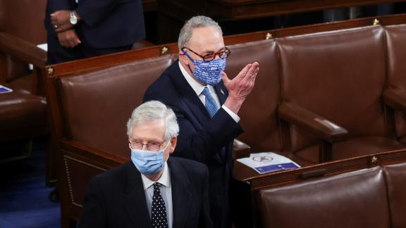 Senate Minority Leader Chuck Schumer blows a kiss to House Speaker Nancy Pelosi as he and Senate Majority Leader Mitch McConnell arrive for the joint session.