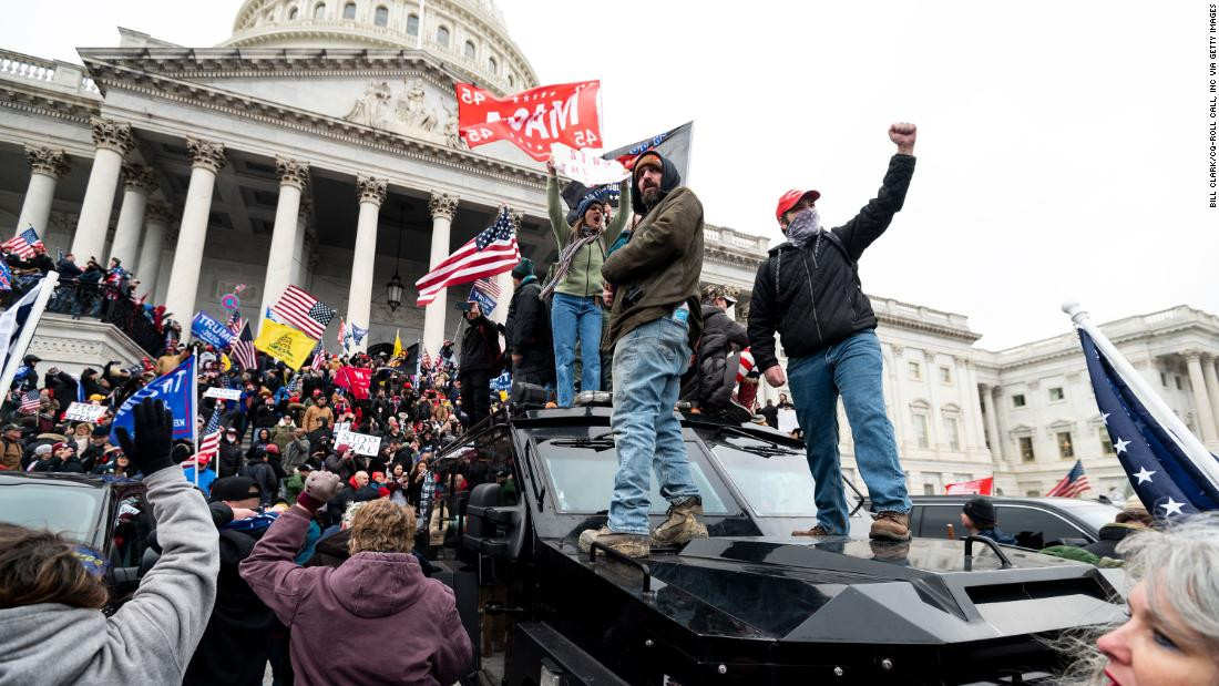 Trump supporters stand on a Capitol Police armored vehicle as others take over the steps of the Capitol.