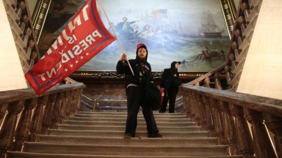 A rioter holds a Trump flag inside the US Capitol near the Senate chamber on Wednesday, January 6.