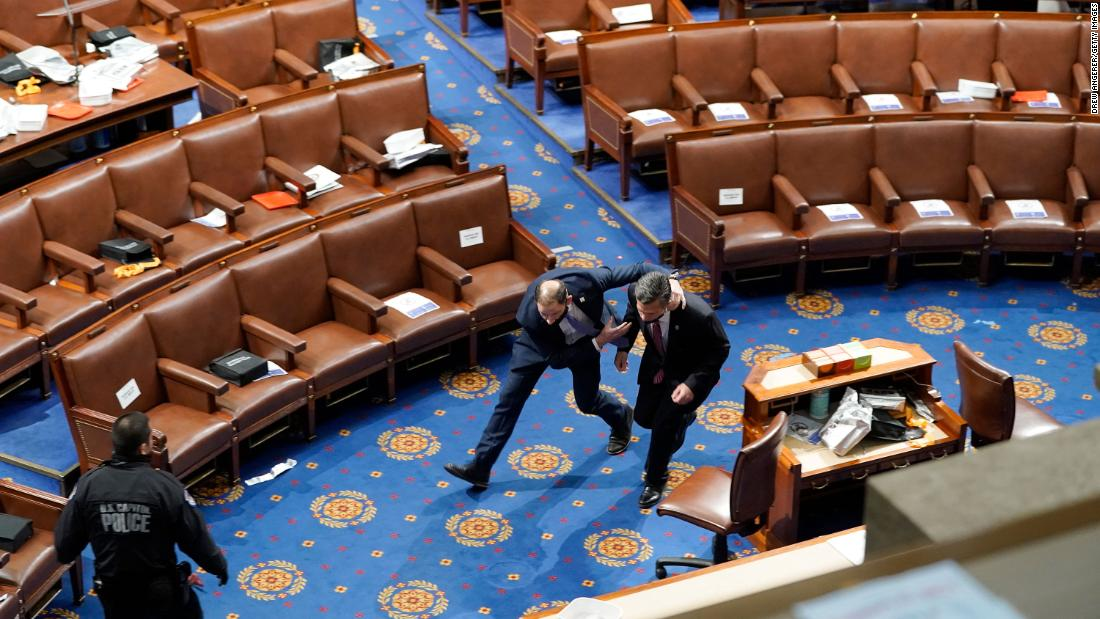 Members of Congress run for cover as rioters try to enter the House chamber.