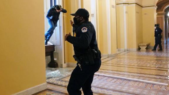 A Capitol Police officer sprays a person who was trying to enter the Capitol.