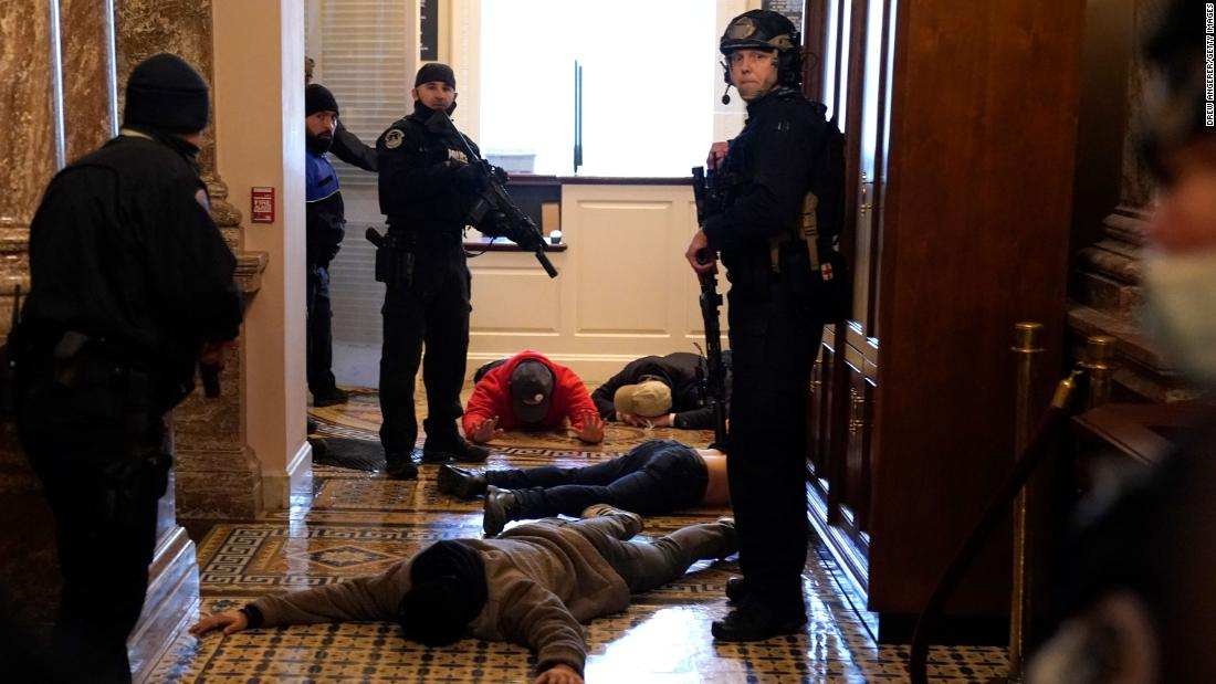 Capitol Police detain rioters outside of the House chamber.