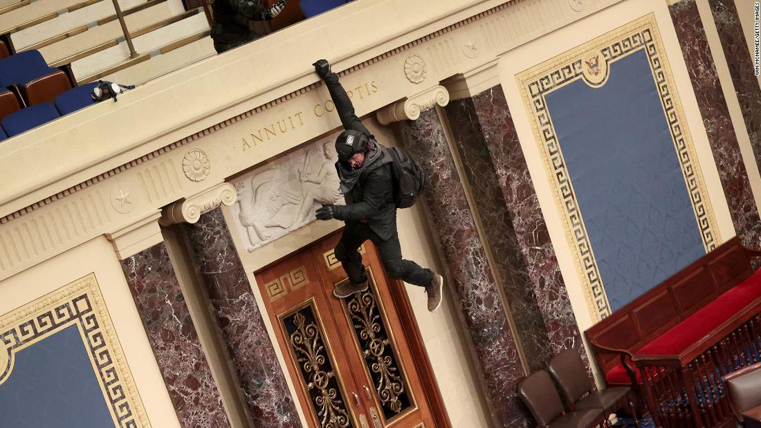 A rioter hangs from a balcony in the Senate chamber.