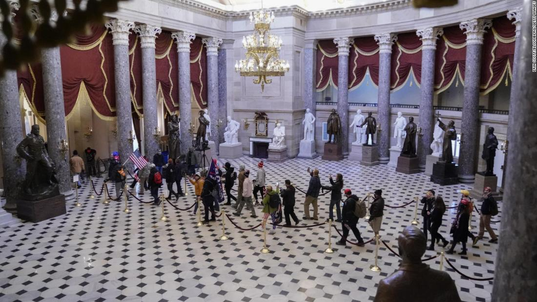 Trump supporters walk through the Capitol's Statuary Hall.