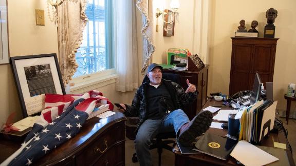 "Richard ""Bigo"" Barnett, the leader of a pro-gun rights group in Gravette, Arkansas, <a href=""https://www.cnn.com/2021/01/07/us/insurrection-capitol-extremist-groups-invs/index.html"" target=""_blank"">sits inside the office of House Speaker Nancy Pelosi.</a> Barnett later showed reporters an envelope that he said he took from Pelosi's desk."