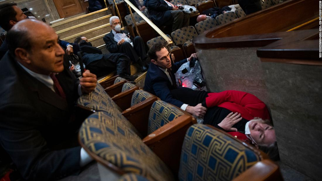 US Rep. Jason Crow, a Democrat from Colorado, comforts US Rep. Susan Wild, a Democrat from Pennsylvania, while taking cover in the House chamber on Wednesday.