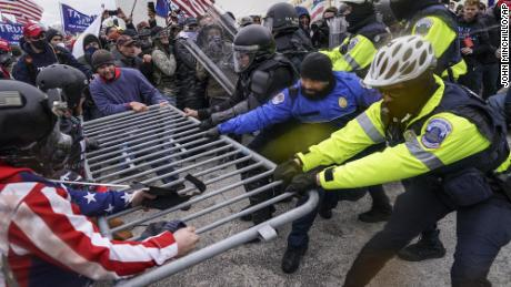 Supporters of President Donald Trump try to breach a police barrier at the US Capitol on January 6, 2021 (AP Photo / John Minchillo)