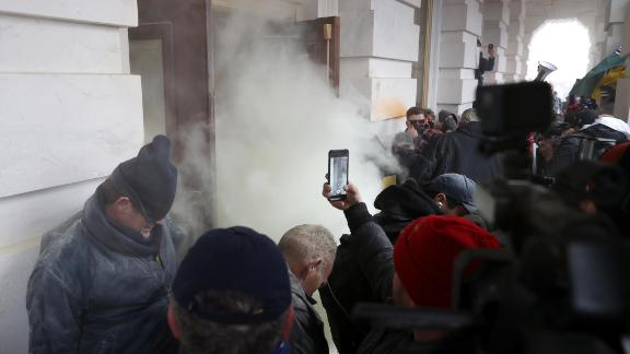 Tear gas is deployed as rioters gather outside the Capitol.