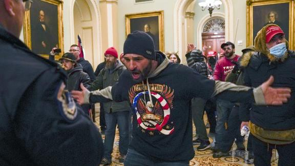 A Trump supporter gestures to Capitol Police in the hallway outside of the Senate chamber.