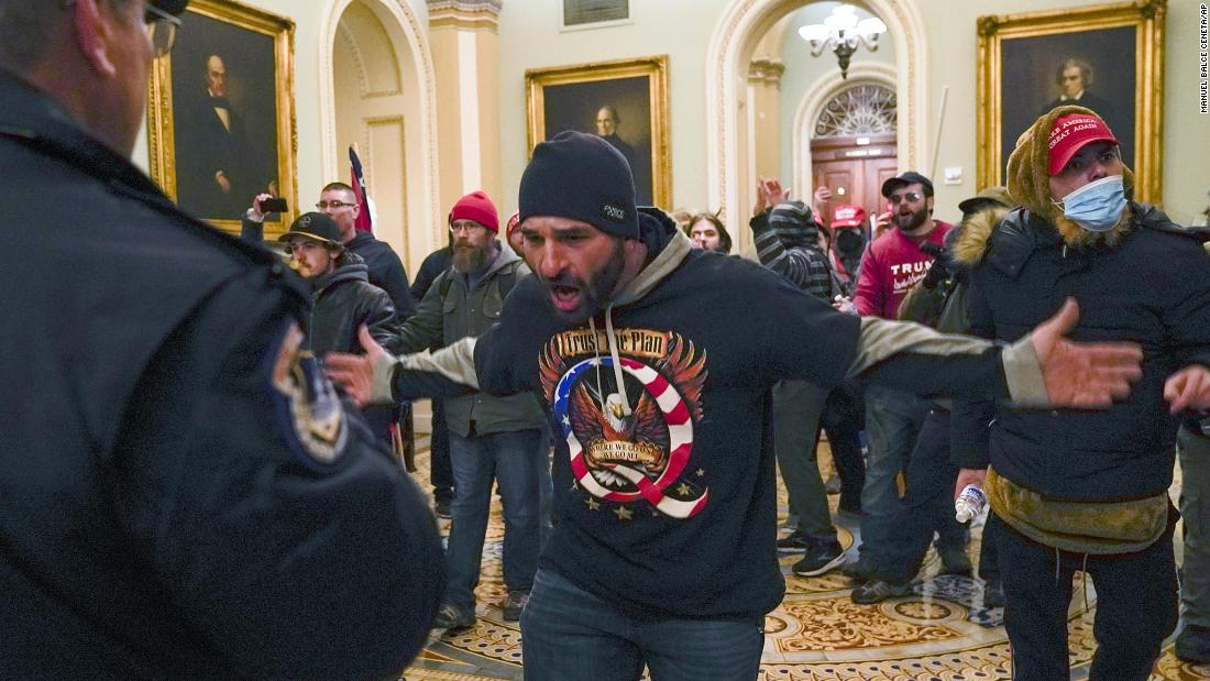Trump supporters gesture to Capitol Police in the hallway outside of the Senate chamber.