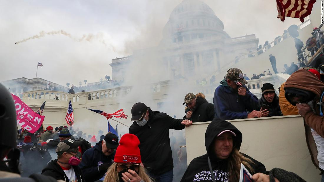 Trump supporters cover their faces after tear gas was fired in front of the Capitol.