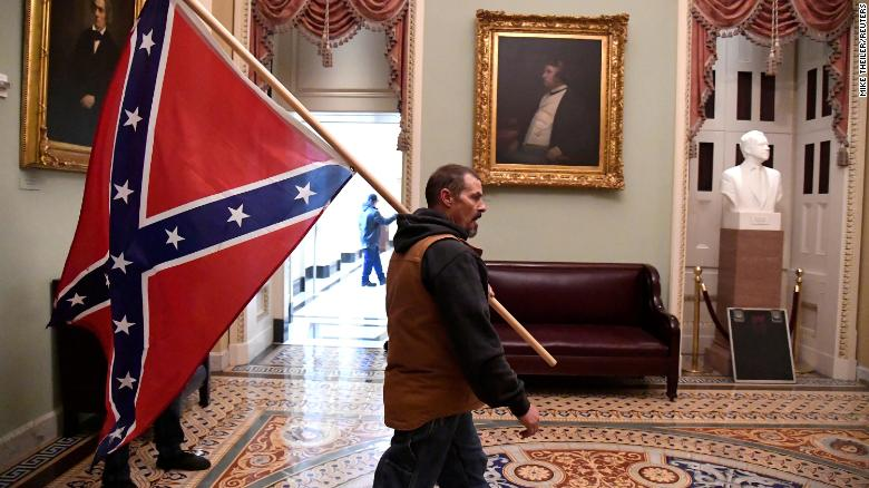 A supporter of President  Trump carries a Confederate battle flag on the second floor of the U.S. Capitol after breaching security defenses, on January 6, 2021.