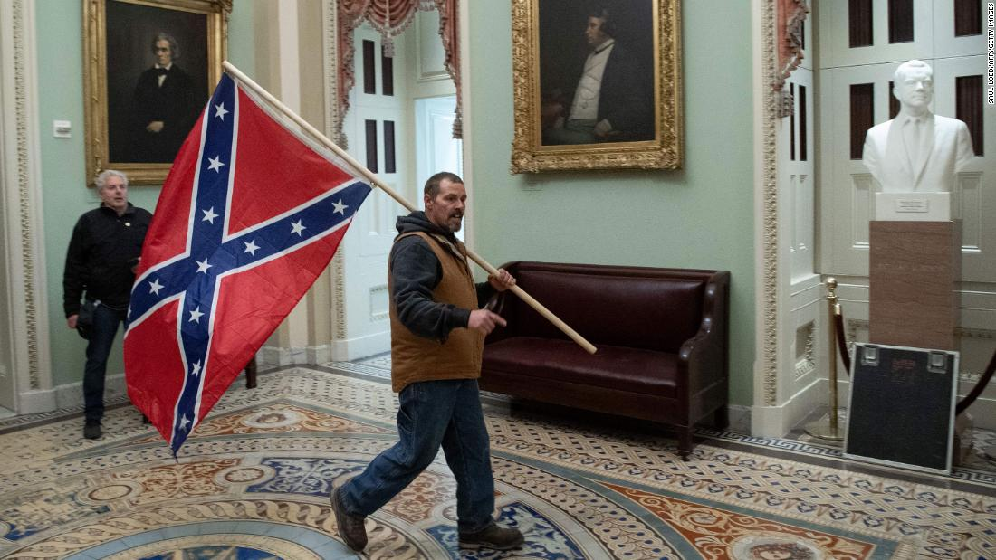 A Trump supporter carries a Confederate battle flag in the Capitol Rotunda.