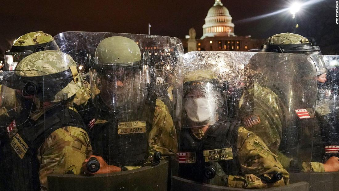 Members of the DC National Guard stand outside the Capitol on Wednesday night after the riots.