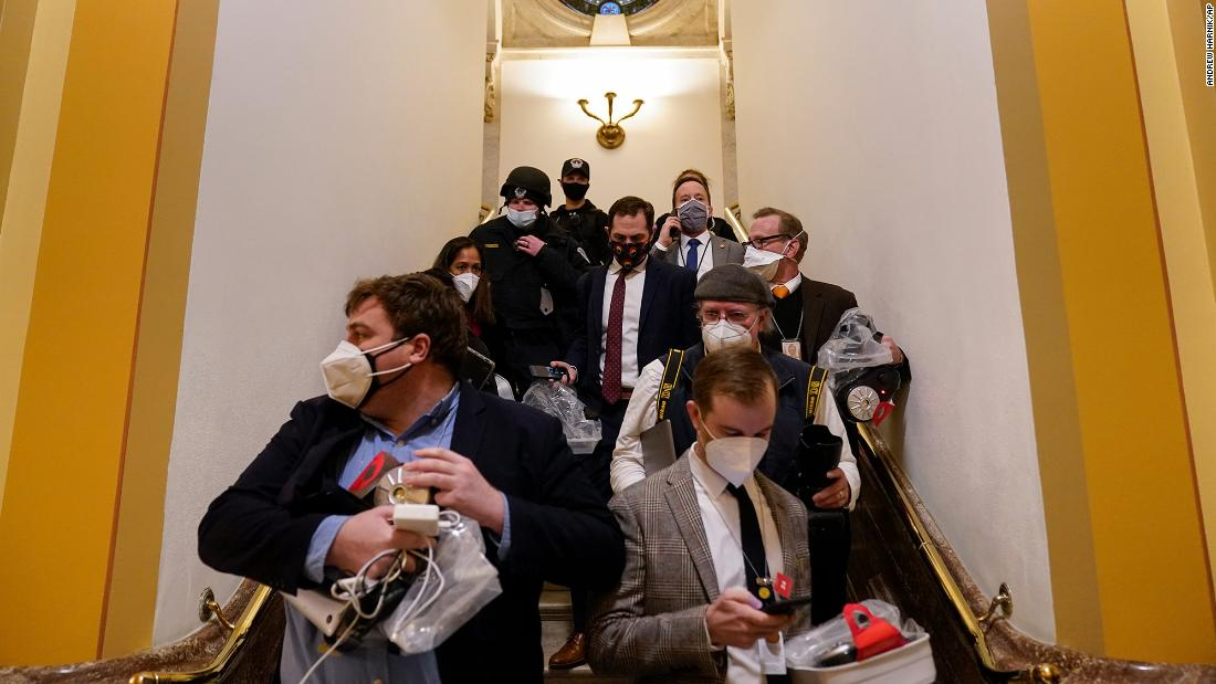 People evacuate the House chamber as rioters attempt to break in.