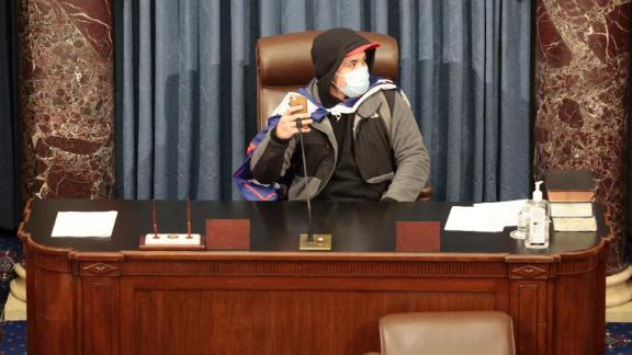 A rioter sits in the Senate chamber.