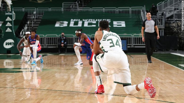 Players from the Bucks and Pistons kneel shortly after the start of an NBA game Wednesday.