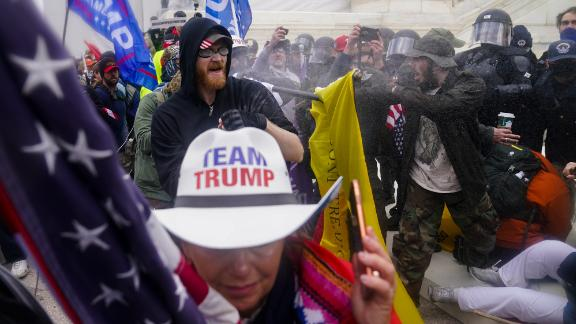 Trump supporters try to break through a police barrier outside the Capitol.