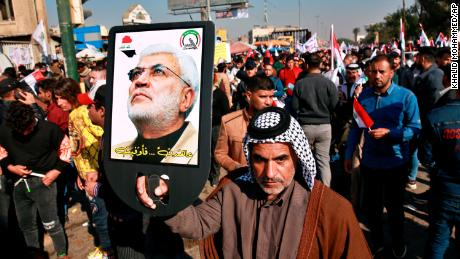 A supporter of Abu Mahdi al-Muhandis, deputy commander of the Popular Mobilization Forces, holds a photo of him during a protest in Tahrir Square, Baghdad, Iraq, Sunday, Jan. 3, 2021.