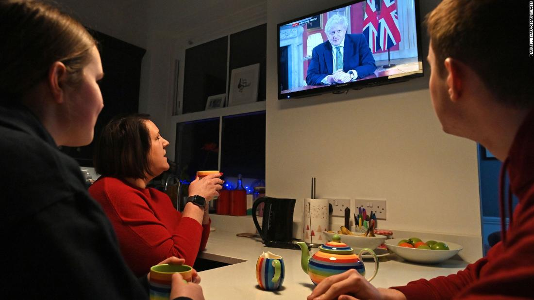 "A family gathers around the television in Liverpool, England, as British Prime Minister Boris Johnson addresses the nation on January 4. <a href=""https://www.cnn.com/2021/01/04/uk/uk-lockdown-covid-19-boris-johnson-intl/index.html"" target=""_blank"">Johnson reimposed a lockdown in England</a> as a more transmissible variant of Covid-19 fueled a surge in infections and hospitalizations in the country."