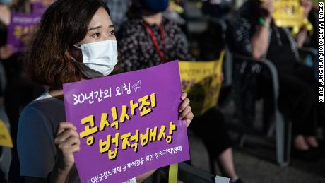At the 2020 International Comfort Women Memorial Day rally in Seoul, South Korea, a woman held up a sign asking Japan to formally apologize and pay compensation.
