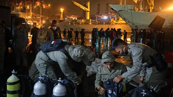 Indonesian police divers check their gear before embarking on a search-and-rescue operation.