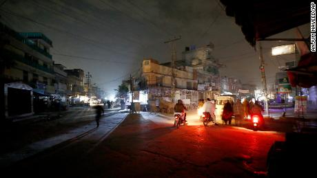 People are silhouetted on vehicles headlights on a dark street during widespread power outages in Rawalpindi, Pakistan, Sunday, Jan. 10, 2021. Pakistan's national power grid experienced a major breakdown late night on Saturday, leaving millions of people in darkness, local media reported. (AP Photo/Anjum Naveed)